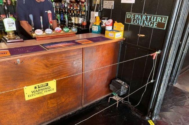 英格蘭康瓦爾郡聖賈斯特市的明星旅店酒吧老闆在吧檯前設置電圍欄。(截自YouTube)