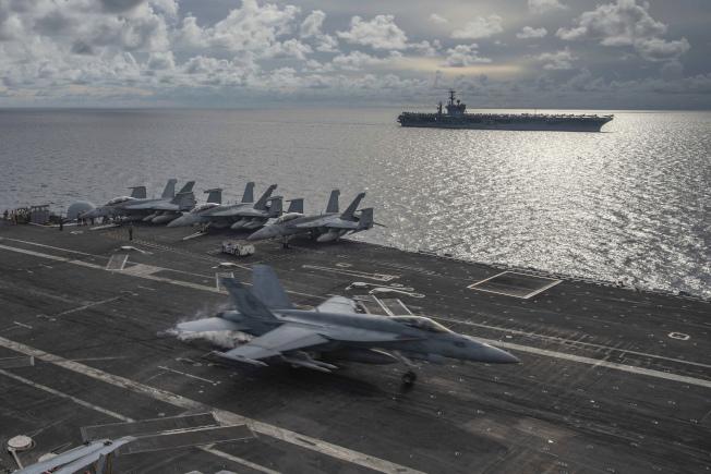甲板上有F/A-18「大黃蜂」戰機的美海軍航母「雷根號」,後為另一艘航母「尼米茲號」,本月6日在重要水道南海,進行少見的聯合軍演。(美聯社)