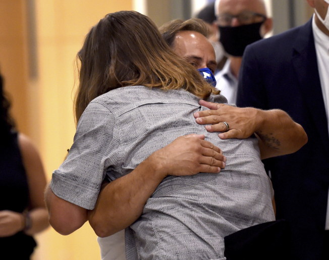 康州法官10日撤銷伯奇(右)與漢寧(左,背對鏡頭)的謀殺指控後,兩人在法院外互擁。(美聯社)