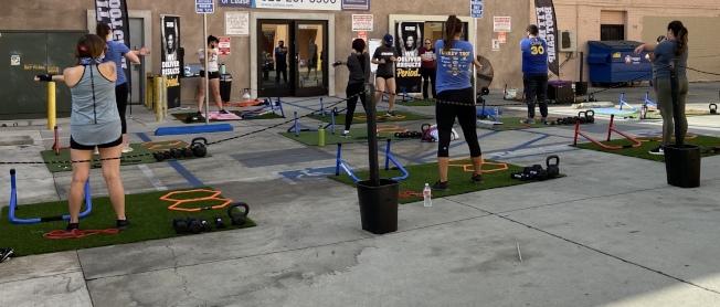 有健身房不被禁令影響,將室內設施移至戶外,利用戶外停車場區域開闢「戶外健身區」。(記者謝雨珊/攝影)