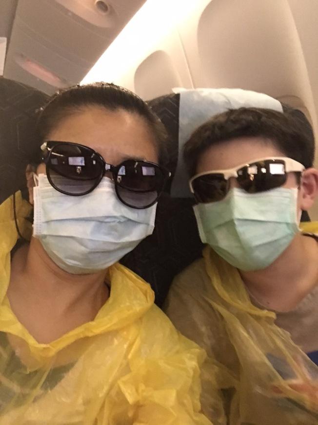 謝婷婷和兒子在飛機上穿雨衣戴墨鏡防疫。(謝婷婷提供)