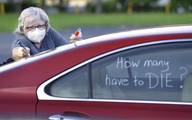 佛州邁阿密市新冠疫情嚴重,已成為全美重疫區中心,有「新武漢」。圖為佛州護士郝爾在參加抗議復學的車隊的車窗上寫著「還要死多人少 ?」。(美聯社)