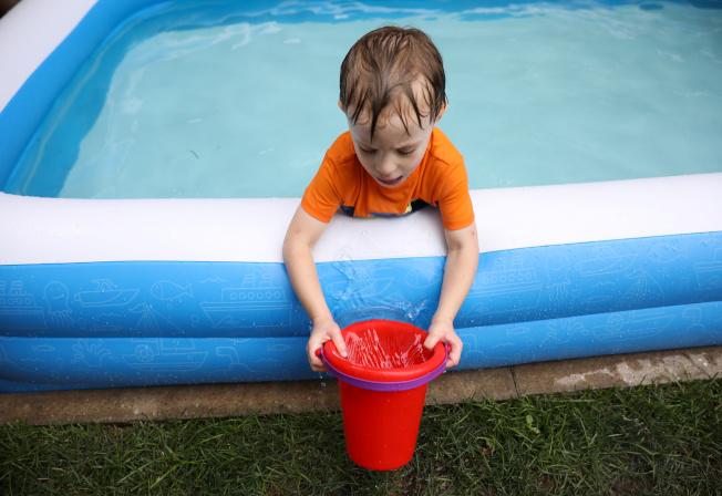 紐約疫情雖緩和,紐約人仍不敢掉以輕心,住在布魯克林的小男孩在自家後院的充氣泳池裡消暑。(路透)