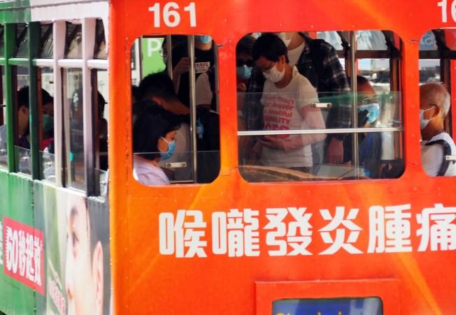 港府15日起強制規定乘坐公共交通的人士必須戴口罩。圖為電車乘客。 (中通社)