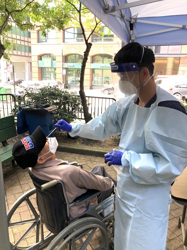 104歲的吳先生(左)15日首次接受新冠肺炎病毒的檢測。(亞美醫師協會提供)