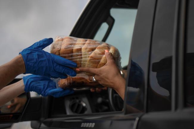 德州聖安東尼奧的「食物銀行」志願者將一袋麵包遞給前來領取食物的市民。德州近日疫情升高,17日是連續第四天確診新增逾1萬例。(路透)