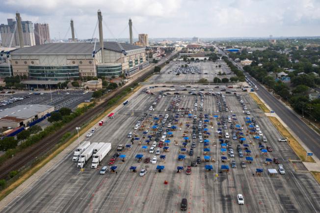 德州聖安東尼奧的「食物銀行」志願者在大停車場發送食物,前來領取食物的車子排成長龍。德州近日疫情升高,17日是連續第四天確診新增逾1萬例。(路透)