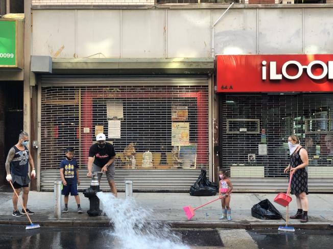 使用路邊的消防栓水管清刷街道。(記者張晨/攝影)