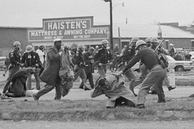 1965年3月7日,路易斯在阿拉巴馬州塞爾瑪鎮(Selma)和平遊行,遭到州警打爆頭骨。照片剛好紀錄下了這一幕。圖中右則跪下的就是路易斯,州警正向他揮去警棍。這天被稱為「血腥星期日」(Bloody Sunday)。(美聯社)