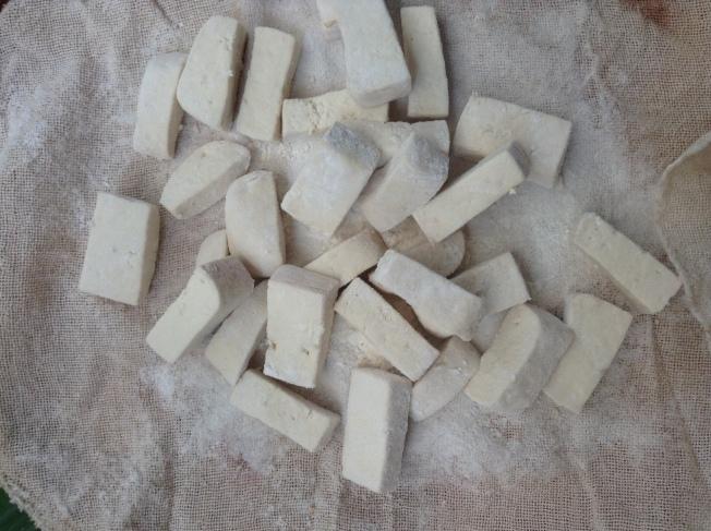 2.在太陽下曝曬2~3小時後,撒上普通麵粉,將豆腐塊包裹起來。