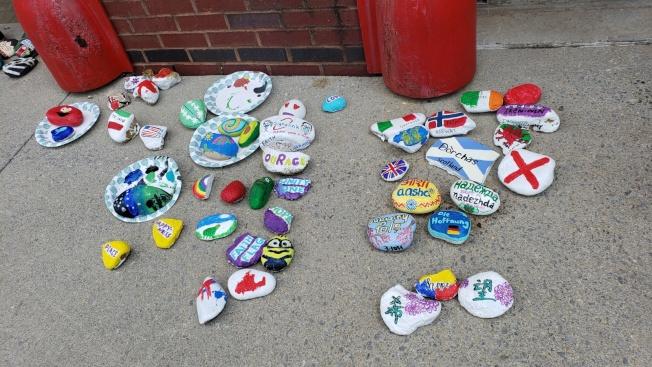 社區人士繪製的五彩繽紛的石頭,展示各國文字的「希望」信息。(記者陳幸蘋/攝影)