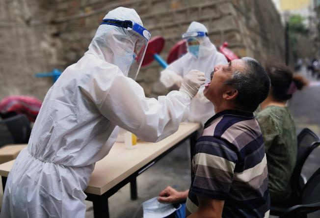 新疆29日新增確診病例96例。圖為烏魯木齊民眾在做核酸檢驗。(中新社)