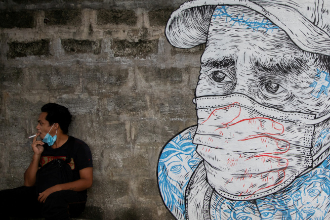 一名男子30日在菲律賓呂宋島奎松市抽菸,旁邊是一幅描繪戴口罩男子的壁畫。(路透)