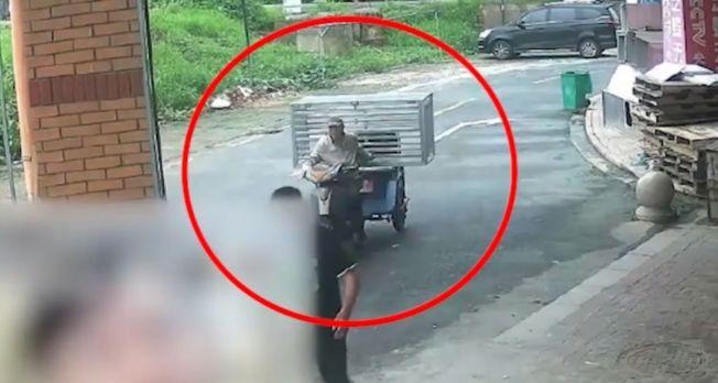 死亡男子曾被监控系统拍到骑车载运铁笼。(视频截图)