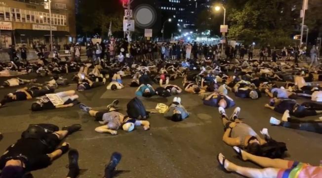 反暴警示威者平躺且林士果,華埠居民憂6月暴亂重現。(讀者提供)