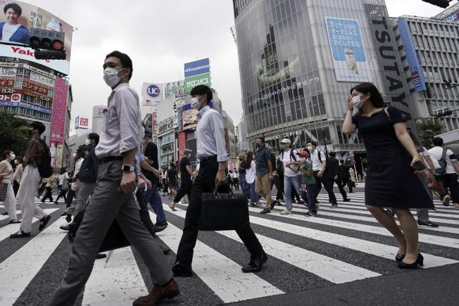日本疫情加重,沖繩將自行宣布進入緊急狀態,並將縣內警示等級從第2階段流行警戒期提升至第3階段感染流行期。圖為東京街頭人人戴口罩。(美聯社)