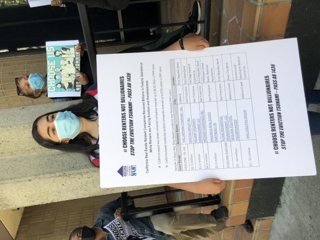 示威者手持一張大表格,上面寫明物業公司收到的PPP計畫的補助數額。(記者劉先進 /攝影)
