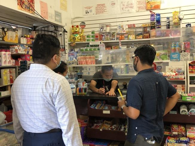 翻譯員將商家面臨的困難傳達給萬齊家(右)。(記者顏潔恩/攝影)