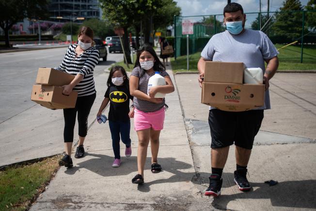 德州一個家庭從食物銀行領取糧食,準備返家。(路透)