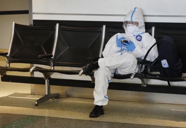 一名中國留學生5月時身著全套防護裝在洛杉磯機場候機。(洛杉磯時報)