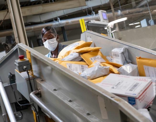 美國郵政系統負荷沉重,疫情期間大批郵件累積,在選民通訊投票比例上升的今年大選,投遞效率受到質疑。(Getty Images)