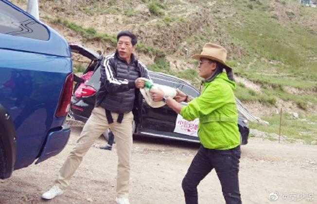 張耀揚(左)在青海貧困區幫忙搬物資。(影片截圖)
