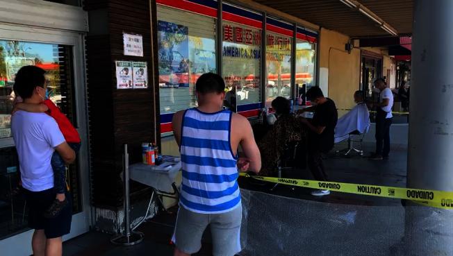 位于罗兰冈的这家华人理发店,也将理发位搬到户外。 (记者李雪/摄影)