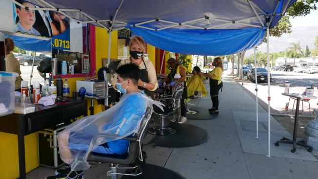 巴市的「Magic Beauty Salon」在发廊店外的人行道边摆理发位,招揽了许多路人的生意。 (记者李雪/摄影)