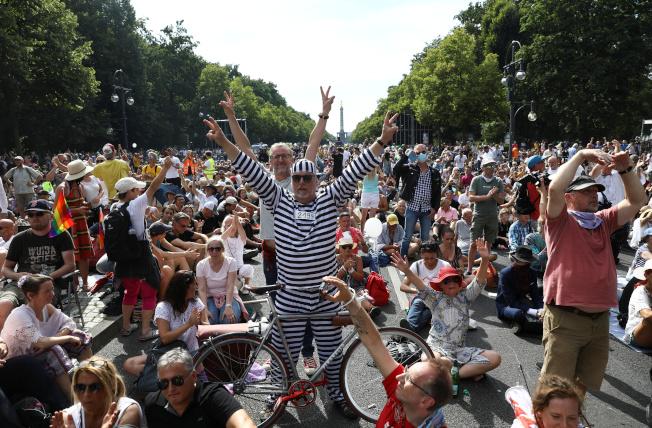 德国首都柏林1日有民众上街抗议,要求解除防疫措施,游行人士几乎都没有戴上口罩。 (路透)