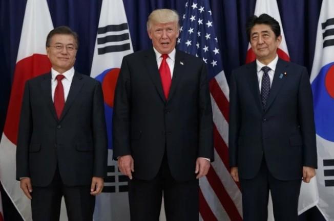 美國總統川普(中)不斷要求亞太地區日韓兩大盟友多負擔軍費,圖為2017年他在德國跟南韓總統文在寅(左)與日相安倍晉三一起見面的畫面。 美聯社