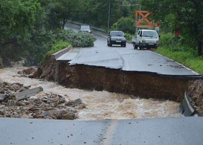 南韓中部強風暴雨成災,忠清北道忠州市2日一處道路坍塌。(歐新社)