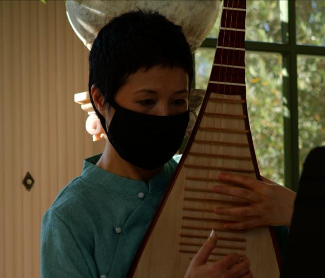 知名的琵琶演奏家Zhang Shenshen戴著口罩演奏曲目。(視頻截圖)