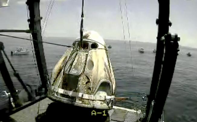 兩名太空人貝肯與赫利乘坐的太空船「飛龍奮進號」,順利降落在墨西哥灣海面後,被Space X公司營救船自海面上吊起。(美聯社)