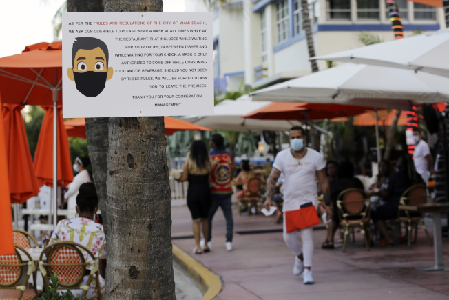 全美新冠肺炎確診病例繼續攀升,即將達到全球第一的500萬例。新的重疫區佛州有些城市已強制要求外出居民要戴口罩。圖為在邁阿密海灘市區,可見市府要大家戴口罩的文宣告示。(美聯社)