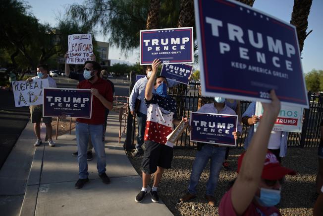 總統大選進入90天倒計時,川普陣營一周敲門百萬,白登陣營則一門未敲。圖為內華達州川普支持者舉牌抗議通訊投票。(美聯社)