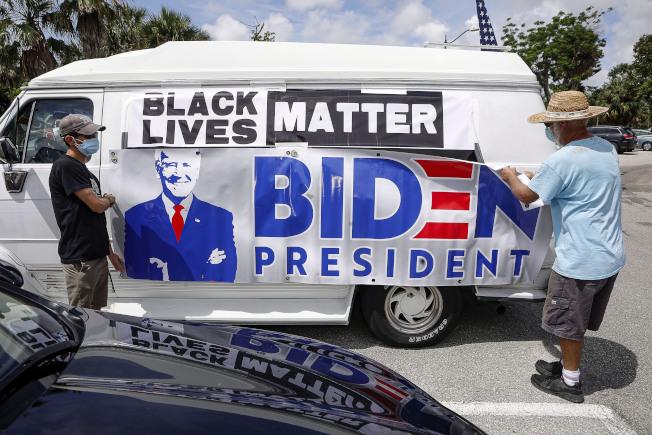 總統大選進入90天倒計時,川普陣營一周敲門百萬,白登陣營則一門未敲。圖為佛羅里達州西棕櫚灘的白登支持者在車上掛出支持白登的橫幅。(美聯社)