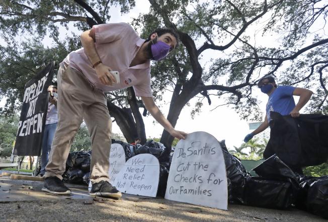 美國人口不到全世界的5%,新冠肺炎確診數和死亡卻占20-25%。但川普總統受訪時卻強調美國經濟的復甦,並且宣稱病毒將「離我們而去」。圖為佛州一團體陳列屍袋和墓碑,抗議州長抗疫不力。 (美聯社)