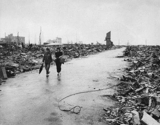 1945年,美軍投放的原子彈在日本廣島引爆後的一個月,兩人行走在殘骸堆中清出的道路上。(美聯社)