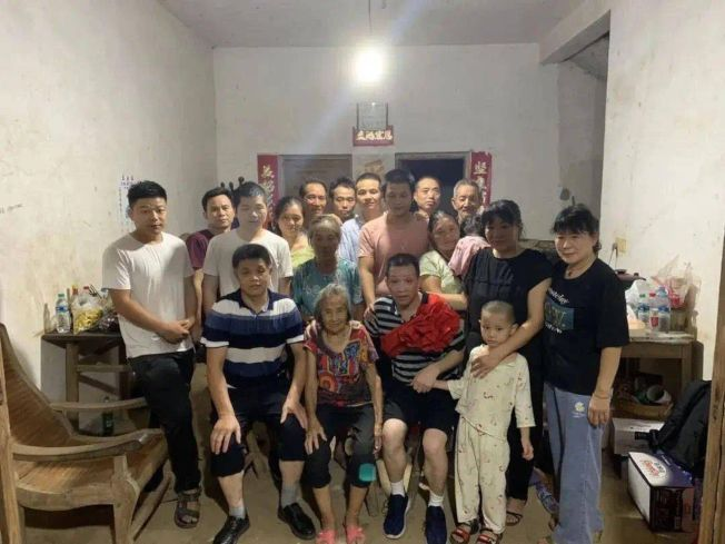 張玉環(前排左三)與母親(前排左二)、哥哥張民雄(前排左一)等家人合拍全家福。(取材自新京報)