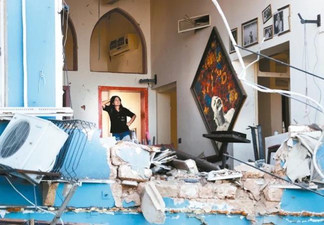 黎巴嫩首都貝魯特4日發生大爆炸,一名婦人5日站在滿目瘡痍的餐廳內,一臉無奈。美聯社