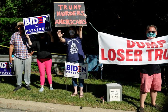 「經濟學人」預測川普總統在大選擊敗白登的機會微小。圖為川普日前訪問俄亥俄州時,白登的支持者舉著反對川普的橫幅和標語。(路透)