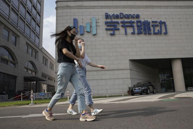 抖音國際版TikTok的母公司「字節跳動」,揚言控告美國政府;圖為民眾走過位於北京的「字節跳動」辦公大樓。(美聯社)