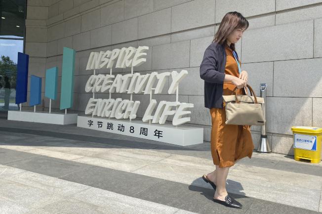 抖音國際版TikTok的母公司「字節跳動」,8日表示打算控告美國政府;圖為一名女子走過「字節跳動」的辦公大樓。(美聯社)