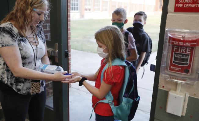 有研究指出,童年接種疫苗可能與人體內有「記憶」T細胞有關。圖為在德州格雷市的小學生進校前規定要戴口罩,接受體溫檢測。(美聯社)