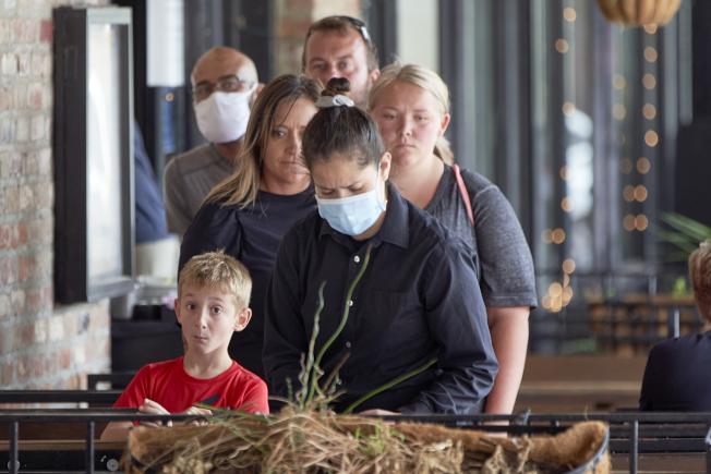 許多人即使染疫也不顯病癥,戴口罩成為唯一避免傳播病毒的辦法。(美聯社)