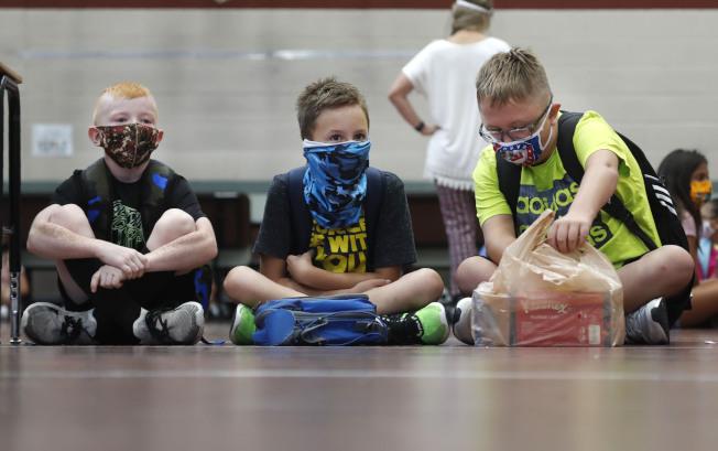 全美各級公私立學校陸續開學,政策不一,學生即使染疫也看不出,校方如何能迅速察覺學生患有新冠疫毒,避免擴大傳染,是一大挑戰。圖為在德州格雷市的小學生進校前規定要戴口罩,接受體溫檢測。(美聯社)