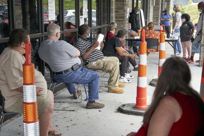 在內不拉斯加州奧馬哈市的就業輔導中心前,戴著口罩的失業工人排隊等著洽談失業補助。(美聯社)