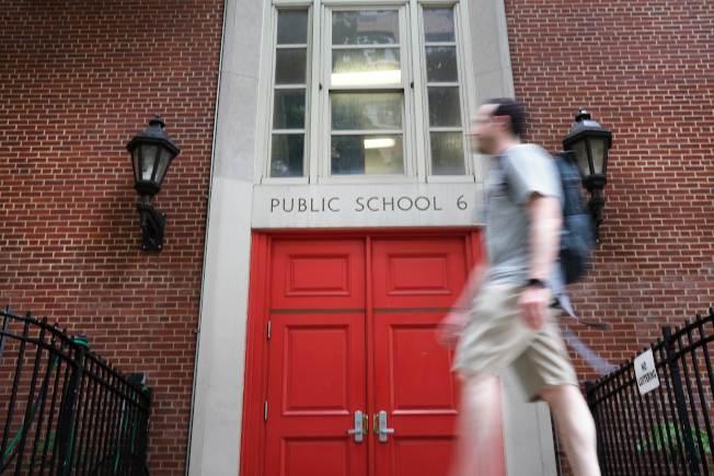 紐約市出台詳盡的秋季復校計畫,圖為一位民眾從曼哈頓上東城一間公立學校門前走過。(Getty Images)