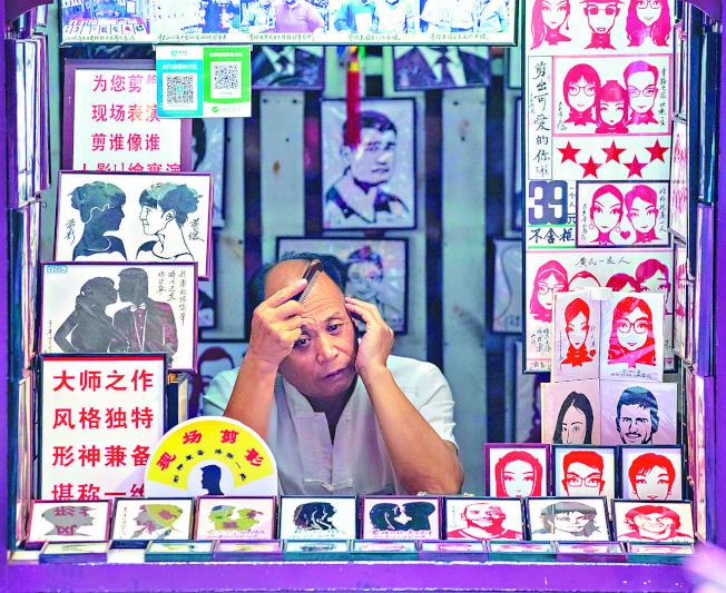 中國經濟漸回暖,但穩企業、保就業仍是主要問題。圖為上海一位剪紙師等顧客上門。(歐新社)