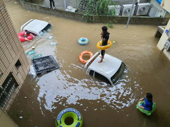 南韓災民8日站在泡水的汽車上等待救援。(歐新社)